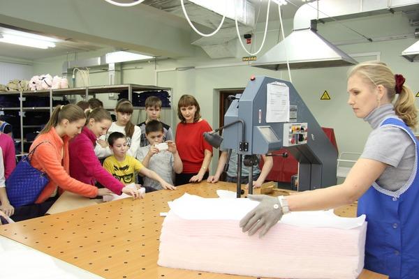 Школьники синтересом наблюдают заработой сотрудников цеха  поремонту ипошиву одежды